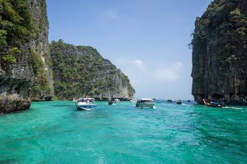Экскурсионные лодки везут туристов по морю, между скал.