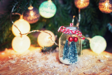 Two small art Christmas trees in a glass jar n front of a Christmas branch decorated with christmas balls