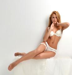 Beautiful bride woman in white lingerie  sitting in bedroom