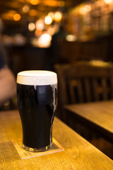 Glass of Dark beer with froth in bar setting