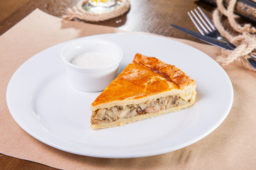 Close up of a single slice of chicken and mushroom pie with sauce on the white plate on the restaurant served table. Selective focus, Space for text.