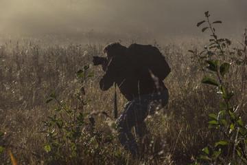 Mann mit Kamera fotografiert die Natur in der Dämmerung