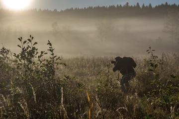 Fotograf fotografiert eine Landschaft im Sonnenaufgang