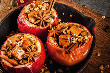 Autumn food recipes. Baked apples stuffed with granola, toffee and spices. On black stone table, in frying pan, copy space