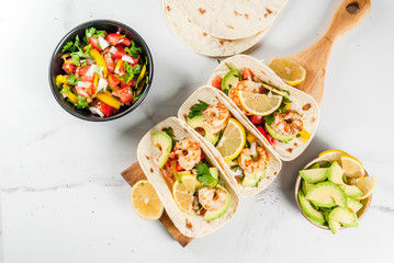 Seafood. Mexican food. Tortilla tacos with traditional homemade salsa salad, parsley, fresh lemon, avocado and grilled shrimp pawns. On a white marble background. Top view copy space