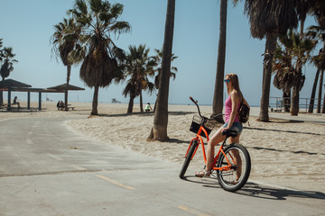 Young girl riding a bike by the Muscle beach in Los Angeles, California, USA.