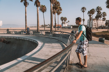 Young man standing by the skate park at the Venice beach in Los Angeles.