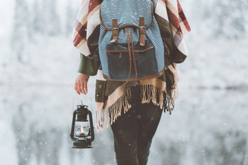 Woman standing in front of amazing lake view with oil lamp. Close-up. Wearing hat, poncho and backpack. Winter is coming, first snowfall. Wanderlust and boho style