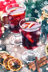 Mulled wine in glasses with spices on wooden table
