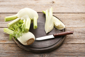 Ripe fennel bulbs with knife on grey wooden table