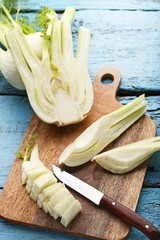 Ripe fennel bulbs with cutting board and knife on blue wooden table