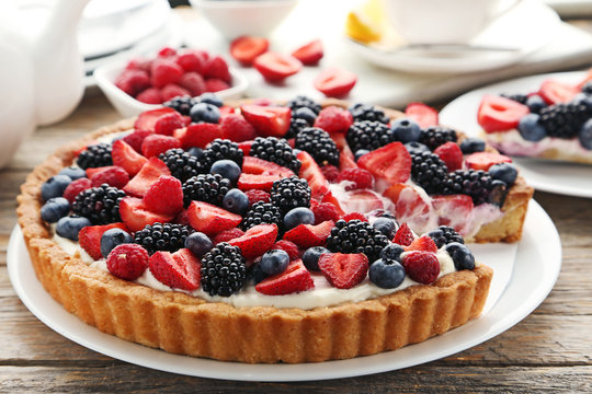 Sweet tart with berries on grey wooden table