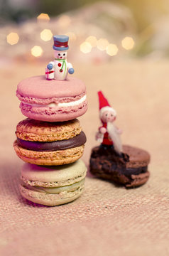 Christmas macaroons, little wooden figurines of snowman and Santa on cookies