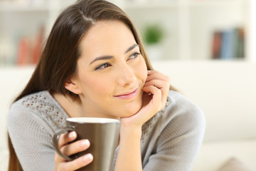 Pensive woman holding a coffee cup looking at side