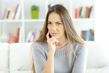 Suspicious woman looking at camera at home