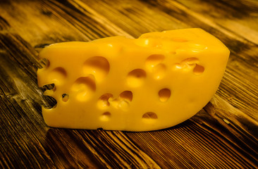 Piece of cheese on wooden table