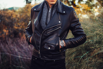 Man wearing black leather jacket and watch posing outdoors Wall mural