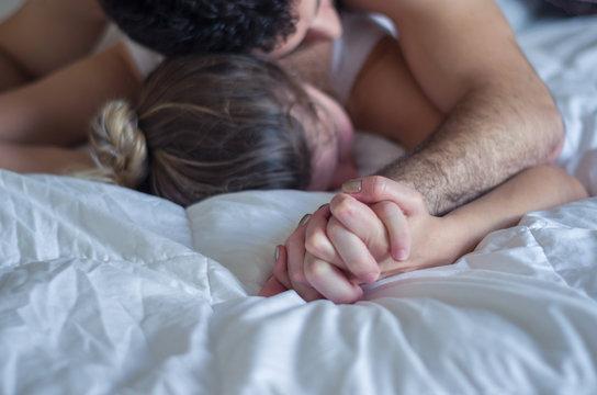 ótimo conceito de orgasmo, sexo, sem vulgaridade, homem segurando mão de mulher na cama