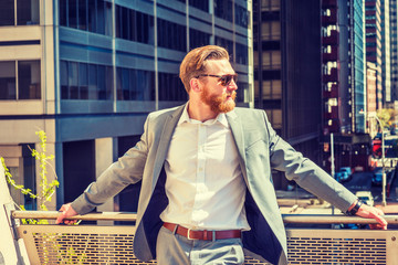 American Man with beard, mustache working in New York, wearing cadet blue suit, white shirt, sunglasses, standing by railing on balcony, facing street with high buildings under sun, waiting to meet.