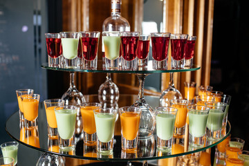 Green and orange cocktails stand on the bar