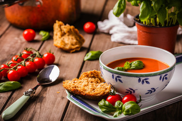 Tomato and basil soup shot on wood boards angled view with vine tomatoes loose basil spoon copper pot basil plant bread landscape
