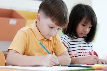 Boy and girl drawing color pencils in kindergarten classroom, preschool and kid education concept