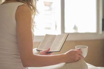 Jovem mulher caucasiana lora lendo livro, bíblia, bebendo café, chá na cama com raios de sol pela janela, manhã cedo.