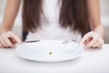 Diet. Suffering from anorexia. Cropped image of girl trying to put a pea on the fork