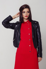 Wall Mural - Young beautiful woman in a black jacket and red dress