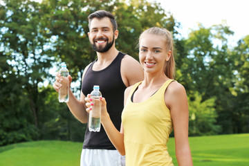 Young sporty couple with bottles of water in green park