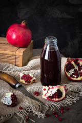 Pomegranate juice in a bottle and pomegranate fruit slices and seeds