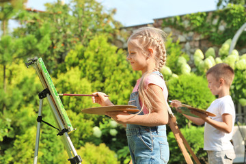 Cute little children painting picture, outdoors