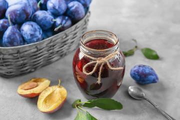 Glass jar with tasty homemade plum jam on table