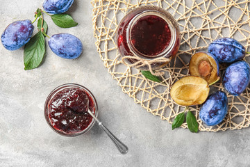 Composition with delicious plum jam on table