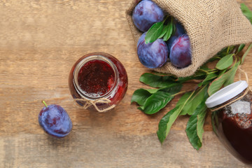 Small sack with ripe plums and tasty jam in jars on wooden table