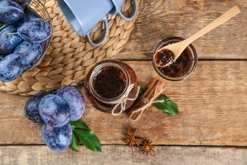 Composition with ripe plums and delicious jam on wooden background