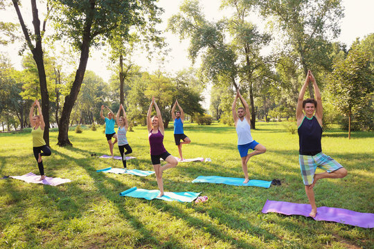Group of young people practicing yoga in park