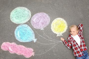 Little girl lying near chalk drawing of air balloons on asphalt