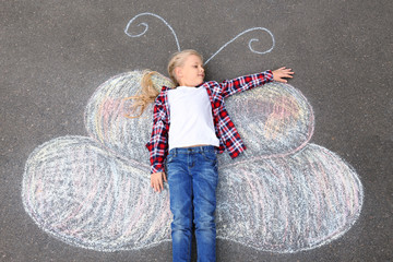 Little girl lying on chalk drawing of butterfly outdoors