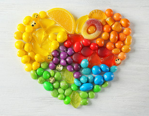 Door stickers Fruits Colorful candies arranged as heart on light background