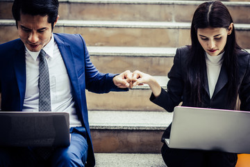 Young business couple sitting on staircase working some before go work on  laptop.