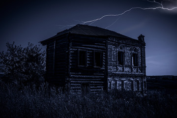 Old abandoned house at night during a thunderstorm.