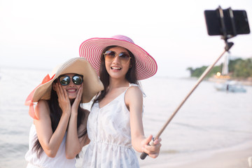 Portrait of Happy traveler Woman Selfie with friend together at beach. Asian women using Smartphone with Happy emotions, Woman with Travel Concept.