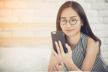 Happy asian girl reading smart phone with smile face on bed .