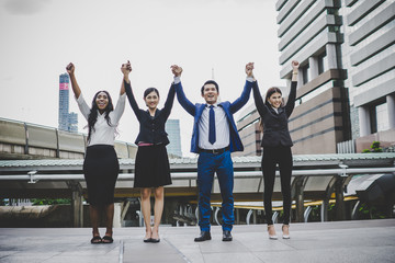 Group of Happy young business people with hands in the air success on their Plans.