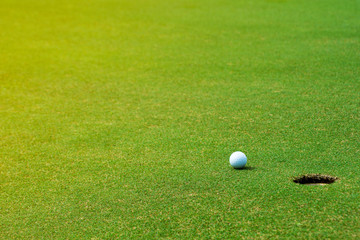 Golf ball on green near golf hole Concept of success, win