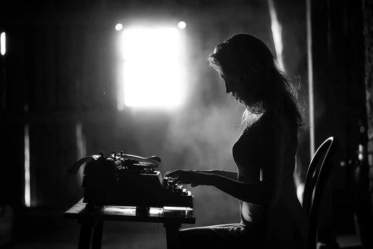 A girl prints on an old typewriter
