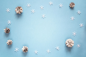 Snow painted pine cones with copy space on blue background. Winter decoration background. Top view, flat lay.