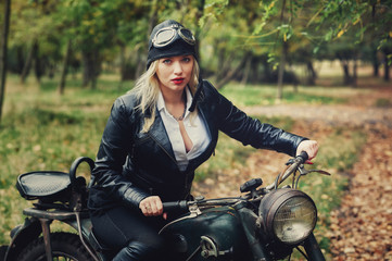 Attractive girl on an old motorcycle in the autumn Park