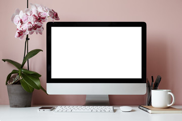 Mock up of creative desktop of female designer with nobody around: modern electronic gadgets, mouse, stationery accessories, notebook, cup and decorative plant against blank pink wall background